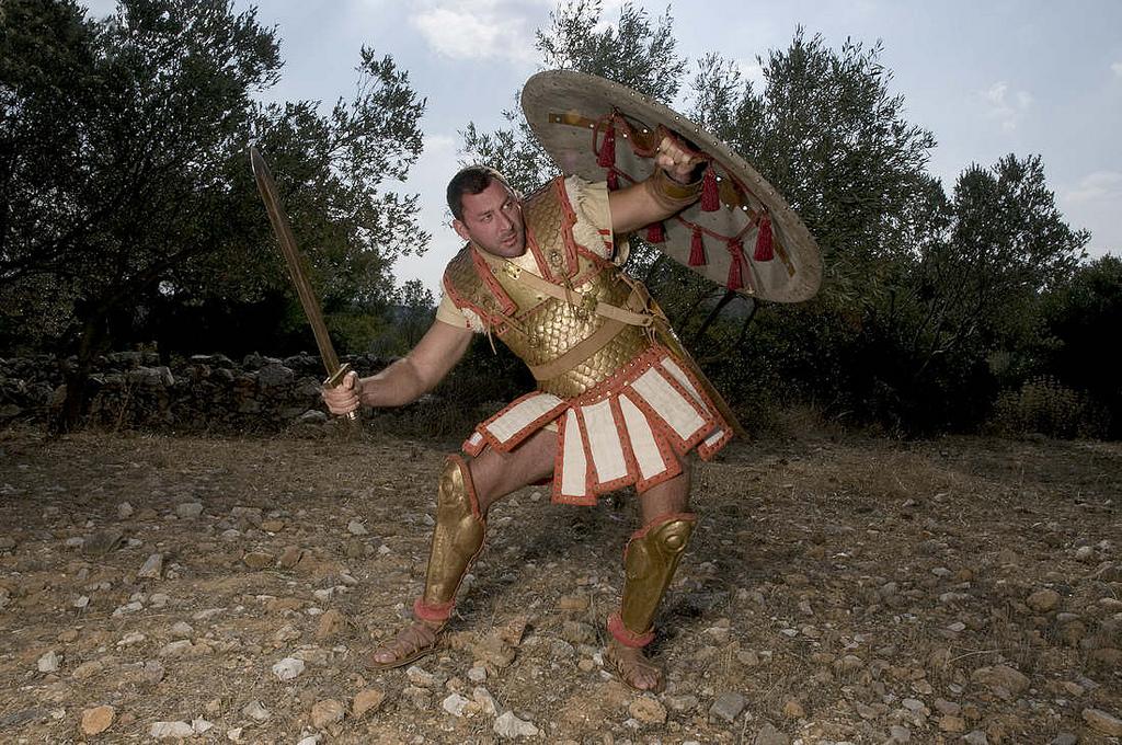 Οπλίτης της Υστερης Αρχαϊκής περιόδου (6ος-αρχες 5ου αι. π.Χ.) με φολιδοθώρακα. Διακρίνεται το εσωτερικό της οπλιτικής ασπίδας. Η εικόνα θα μπορούσε να αντιστοιχεί τοσο σε Κυμαίο, όσο και σε Ετρούσκο οπλίτη (ευγενική χορηγία του Συλλόγου Ιστορικών μελετών 'Κορύβαντες' – η οπλοσκευή είναι έργο του δημιουργού Δημήτρη Κατσίκη).