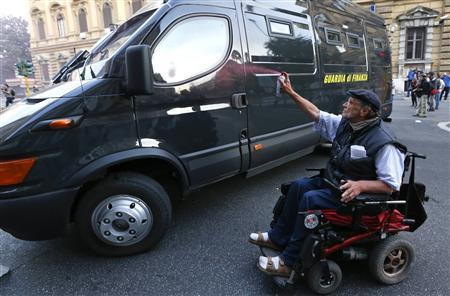 A demonstrator on a wheelchair sprays an Italian finance police van during a protest in downtown Rome