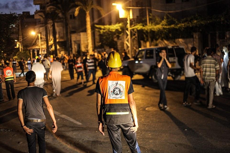 Παλαιστίνιοι πυροσβέστες μπροστά από τα συντρίμμια του κτιρίου al-Zafer