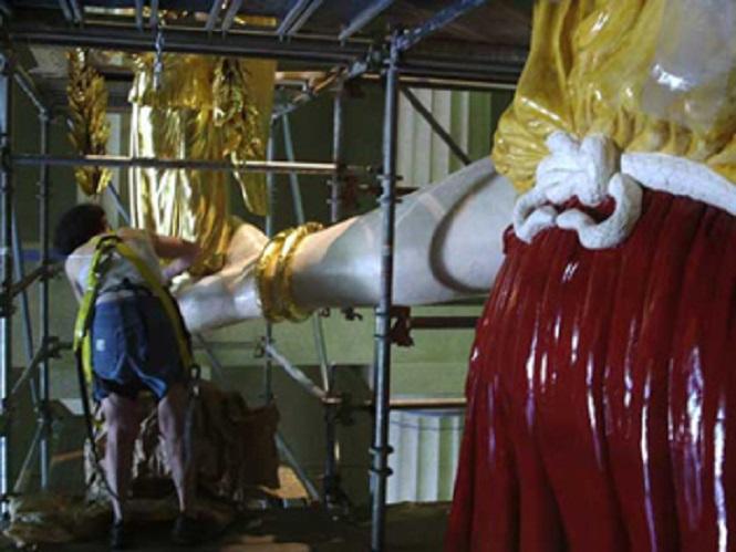 Λεπτομέρεια του μπροστινού μέρους του γλυπτού, όπου συνδυάζονται όλες οι φάσεις ετοιμασίας του : 1.κίτρινη γομαλάκα στο πάνω μέρος του φορέματος, 2. κόκκινο μίγμα συγκρατήσεως στο κάτω μέρος,