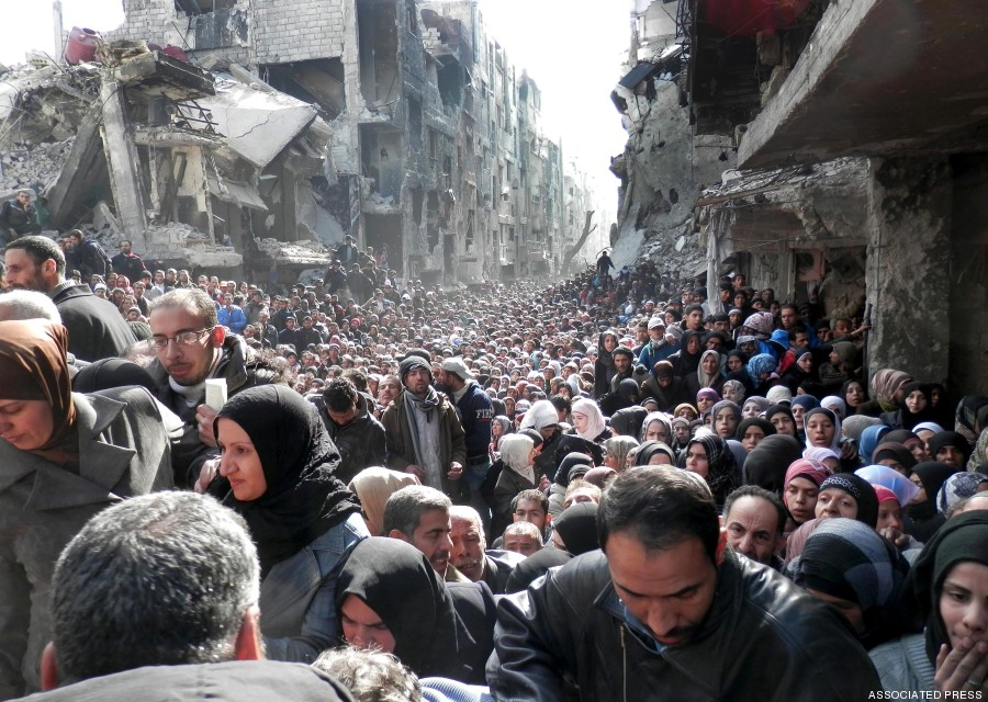 This picture taken on Jan. 31, 2014, and released by the UNRWA, shows residents of the besieged Palestinian camp of Yarmouk, queuing to receive food supplies, in Damascus, Syria. A United Nations official is calling on warring sides in Syria to allow aid workers to resume distribution of food and medicine in a besieged Palestinian district of Damascus. The call comes as U.N. Secretary General Ban Ki-Moon urged Syrian government to authorize more humanitarian staff to work inside the country, devastated by its 3-year-old conflict. (AP Photo/UNRWA)