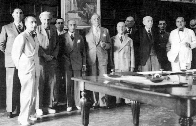 Το διοικητικό συμβούλιο της Εθνικής Λυρικής Σκηνής το 1944. Μία από τις ελάχιστες γνωστές φωτογραφίες, όπου εικονίζεται ο Ιωάννης Βουλπιώτης επί Κατοχής (τέταρτος από αριστερά, ανάμεσα στον Μανώλη Καλομοίρη και τον Ιωάννη Αθανασιάδη, πρόεδρο του Δημοτικού Συμβουλίου Αθηναίων τότε). Ανάμεσα στους άλλους εικονιζόμενους, στο κέντρο ο κατοχικός πρωθυπουργός Ιωάννης Ράλλης, πρώτος αριστερά ο Οδυσσεύς Λάππας, από δεξιά ο Τίμος Μωραϊτίνης, ο Άγγελος Τερζάκης, ο Νικόλαος Λάσκαρης και ο Θεόδωρος Συναδινός.