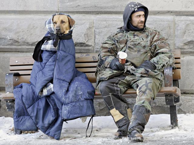A man who identified himself as Mario sits with his dog, Spliff, as they bundle up against the -15C, 5F temperatures as he panhandles in downtown Montreal, Canada Thursday, March 10, 2005.(AP Photo/Ryan Remiorz)