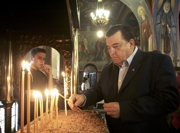 Far-right LA.O.S party President Karatzaferis lights a candle inside an Orthodox church in Athens