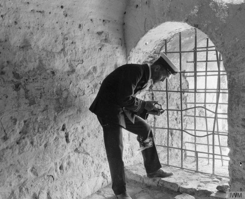 Lieutenant Commander Ernest Gardiner R.N.V.R. examining broken pottery in the White Tower, Salonika 1916. At this time the White Tower was used to house the British Salonika Force archaeological collection. In peace time Gardiner had been Director of the British School at Athens (1887-1895) and Professor of Archaeology at the University of London (1896-1902).