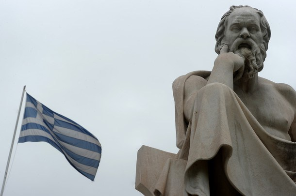 A Greek flag flies next to a statue of a