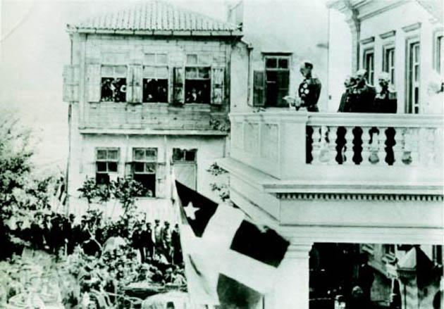 Διακρίνεται η σημαία της Κρητικής Πολιτείας σε ομιλία του Πρίγκηπα Γεωργίου, κατά την ανακήρυξη της ανεξαρτησίας της Κρήτης.